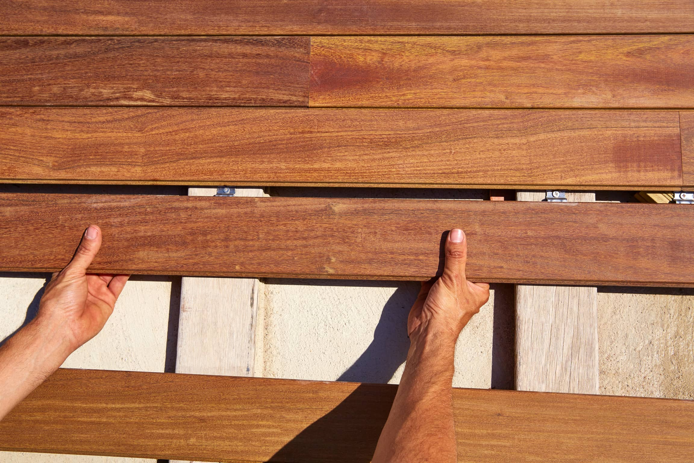 An image of a contractors hands piecing together flooring for a deck.