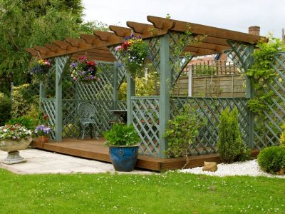 This is an image of a beautiful garden pergola with sitting area and table underneath.