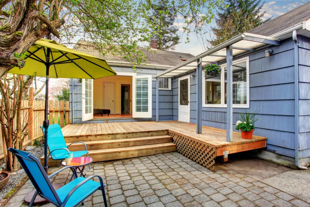 A picture of a blue house with a wooden porch with steps in the back yard area.
