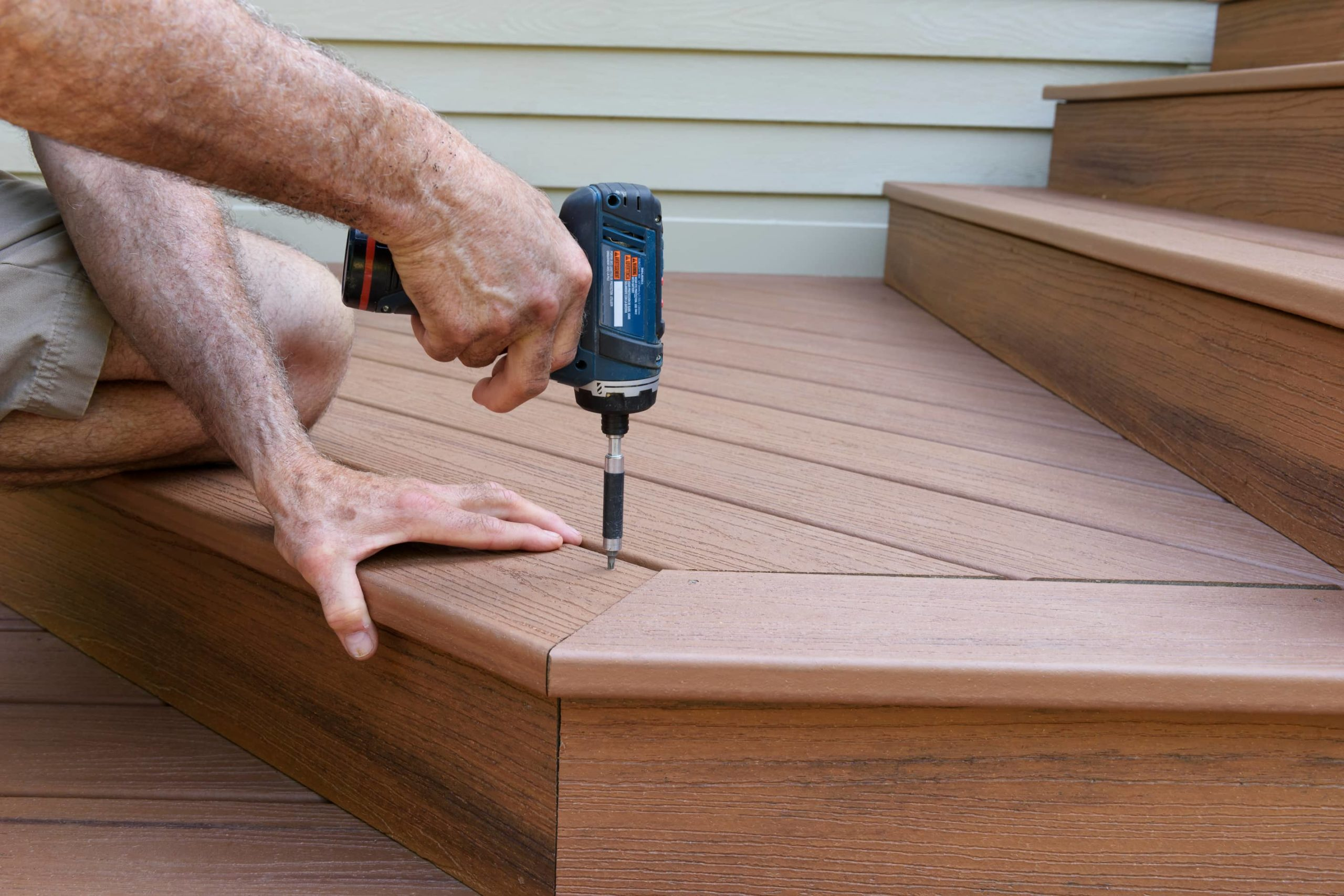 This image shows a man using a power drill to install a new deck for a home.